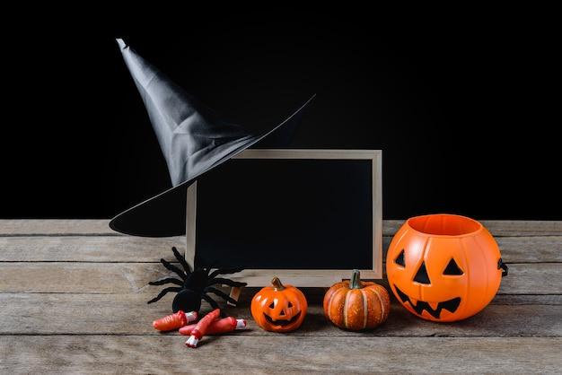 Die tafel auf dem stand, hexenhut, schwarze spinne mit halloween pumpkins