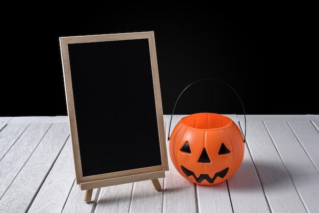 Die tafel auf dem stand mit halloween pumpkins auf bretterboden und schwarzem hintergrund