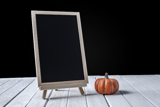 Die tafel auf dem stand mit halloween pumpkins auf holzboden