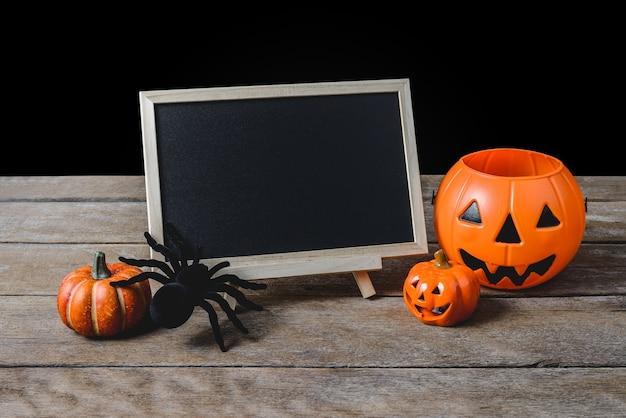 Die tafel auf dem stand mit halloween pumpkins, schwarze spinne auf bretterboden