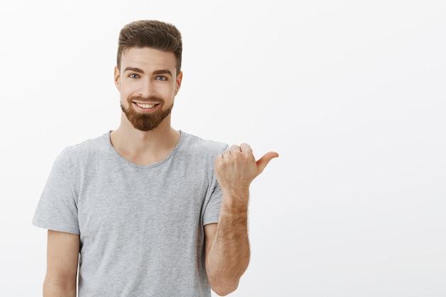 Die taille des hübschen, stilvollen und maskulinen, selbstbewussten mannes mit bart und weißem, süßem lächeln, das mit dem daumen nach rechts zeigt, um den kopierraum zu gewährleisten, ist perfekt mit selbstbewusstem, entzücktem ausdruck