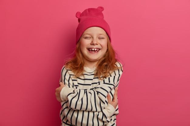 Die taille eines überglücklichen kleinen mädchens umarmt sich, verschränkt die arme vor dem körper, lacht, trägt einen rosa hut und einen gestreiften pullover, drückt selbstliebe aus, hat schicke haare und schließt mit großer freude die augen