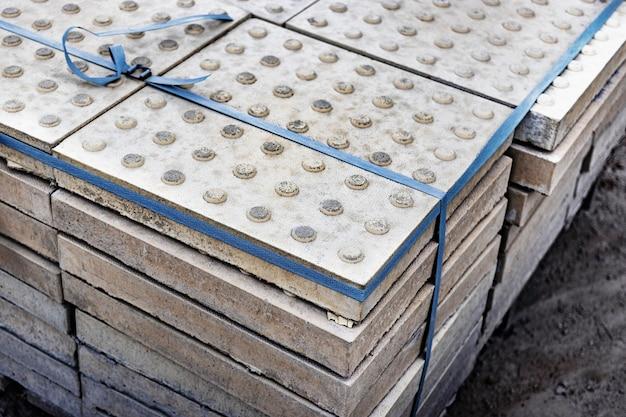 Die taktile textur von pflastersteinen vor dem verlegen auf der straße. blindenschutz auf geh- und gehwegen.