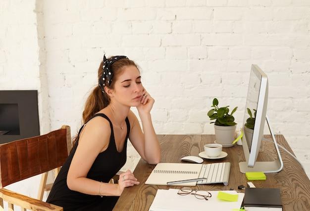 Die talentierte junge designerin denkt über das design eines neuen cafés nach, das zu hause freiberuflich arbeitet. attraktive kaukasische junge frau mit nachdenklichem gefühl auf einem gesicht, das am arbeitsplatz nachdenklich aussieht
