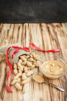 Die tasche der rohen erdnüsse in der schale, glasschale der erdnussbutter auf hölzernem hintergrund mit kopienraum. flatlay. heidiges essen.