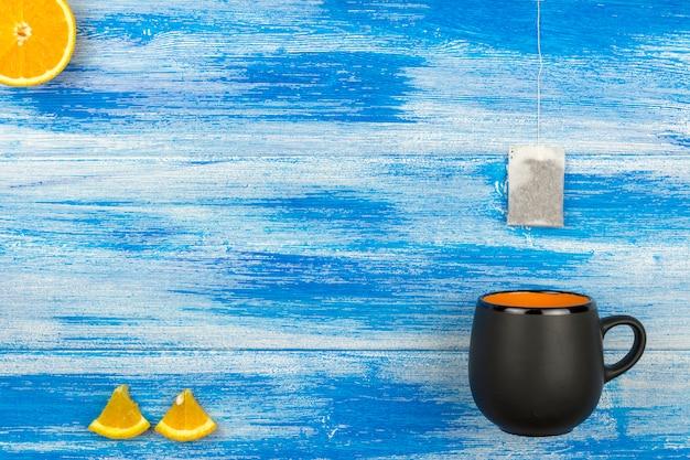Die tasse tee auf einem blauen hintergrund. teebeutel und orangenscheiben