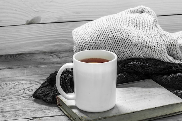 Die tasse tee auf einem schönen hölzernen hintergrund mit winterpullover, altem buch, winter, herbst, nahaufnahme
