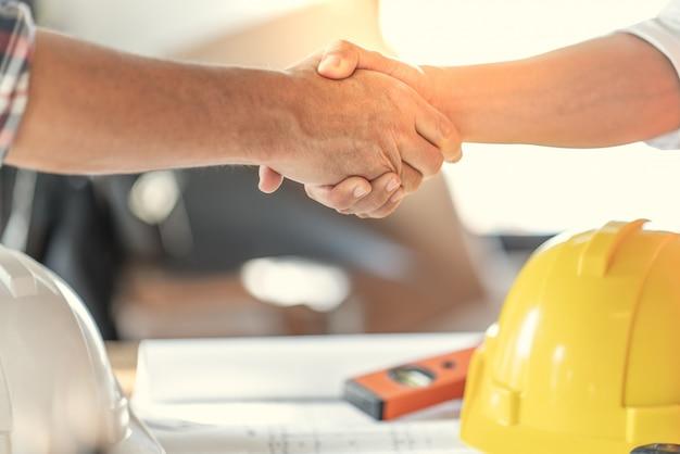Die teamarbeit der offiziere ist glücklich und reicht die hand, um den erfolg des abschlusses der jobplanung zu feiern