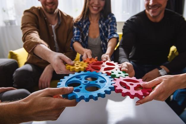 Die teamarbeit von geschäftsleuten arbeitet zusammen und kombiniert zahnradteile