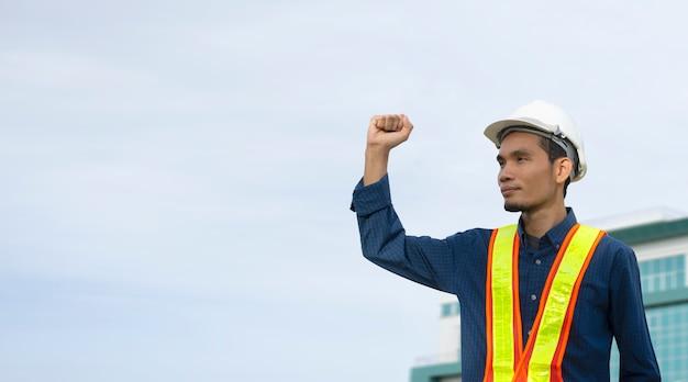 Die technik, die handerfolg hält und trägt einen weißen sicherheitshut beim arbeiten.