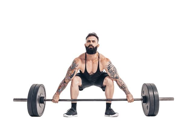 Die technik, eine kreuzhebenübung mit einer langhantel eines muskulösen, stark tätowierten bärtigen sportlers durchzuführen