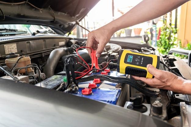 Die technik verwendet das instrument, um die spannung und temperatur der autobatterie zu messen.