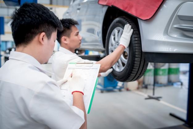 Die techniker führen die fahrzeugüberprüfung durch und machen notizen für den fahrzeughalter