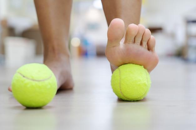 Die tennisballbehandlung: der ball übt druck auf die schmerzende stelle aus und hebt das verfahren an.