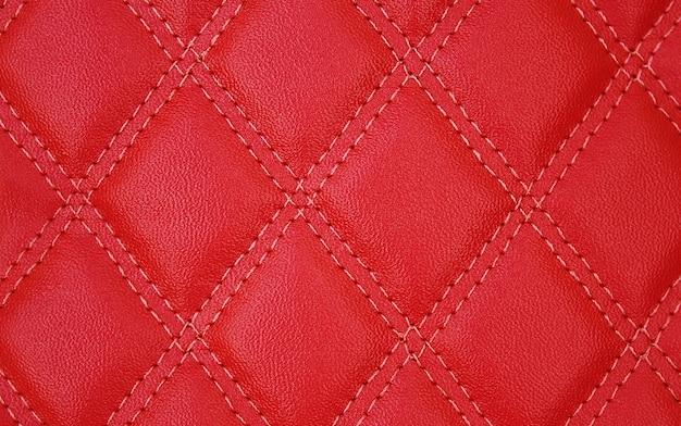 Die textur aus rotem leder ist mit fäden in form eines diamanten bestickt.