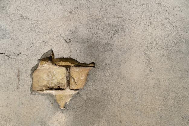 Die textur der gebäudehülle mit einem stück, das mit einer lücke auf einer bröckelnden mauer herausfällt
