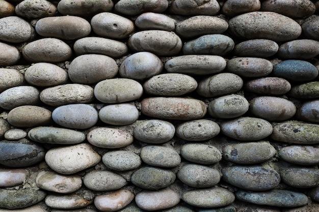 Die textur der steinmauer, mauerwerk aus natürlichen ovalen steinen.