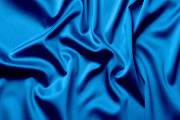 Die textur des satinstoffs in blauer farbe für den hintergrund