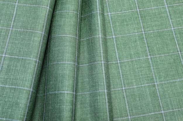 Die textur des seidenstoffs in einem hellgrün-blauen karo. hintergrundmuster