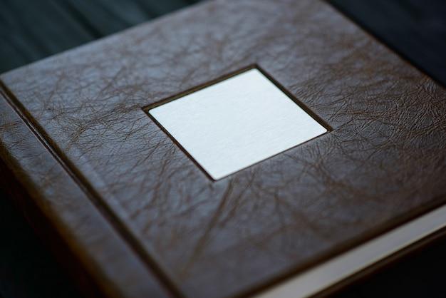 Die textur des umschlags eines fotobuchs aus echtem braunem leder auf einem schwarzen holztisch.