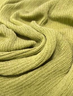 Die textur des weichen strickstoffs ist wie ein gelber hintergrund.
