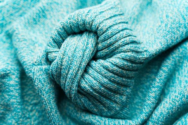 Die textur einer blauen türkisfarbenen maschenware. zerknitterter strickjackehintergrund