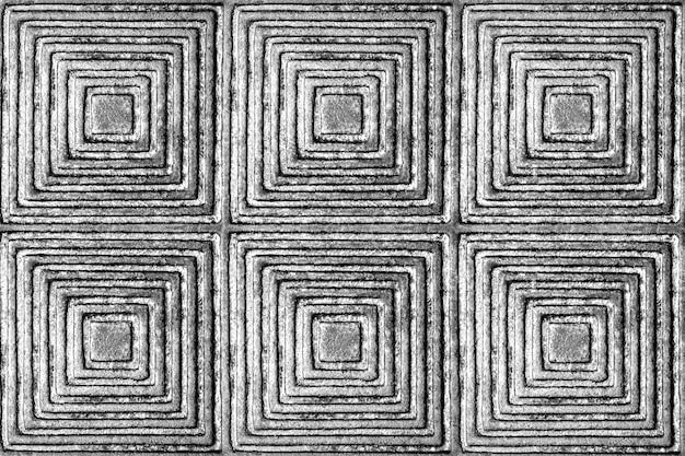 Die textur einer metalloberfläche mit einem muster in form von quadraten und rauten in schwarz und weiß.