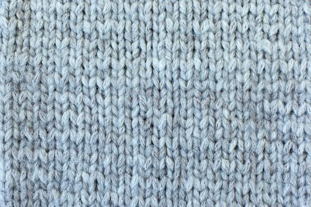 Die textur eines gestrickten wollstoffs grau. hintergrund