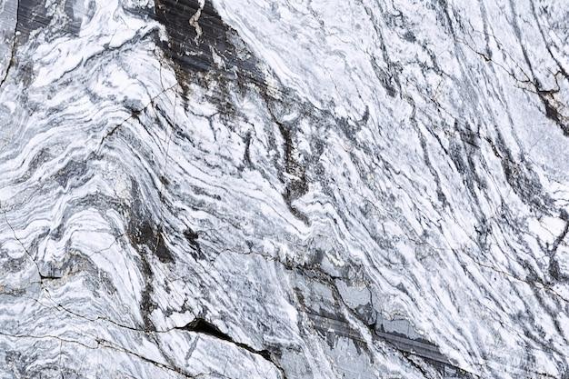 Die textur eines marmorfelsens mit rissen