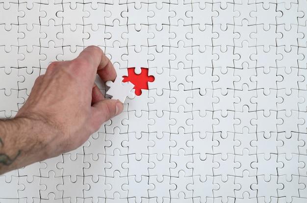 Die textur eines weißen puzzlespiels im zusammengebauten zustand mit einem fehlenden element, das die männliche hand einfügt