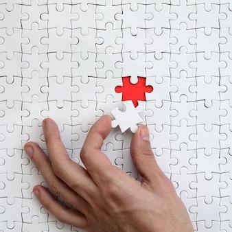 Die textur eines weißen puzzlespiels im zusammengebauten zustand mit einem fehlenden element