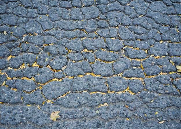 Die textur von altem asphalt mit rissen.