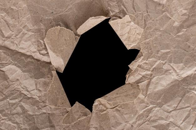 Die textur von zerknittertem bastelpapier mit einem loch