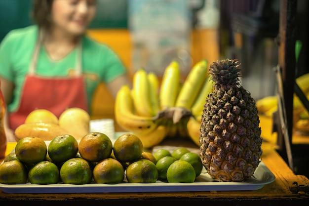 Die thailändische verkäuferin verkauft obst, bananen, mangos, mandarinen und ananas in einem supermarkt in der khao lak street.
