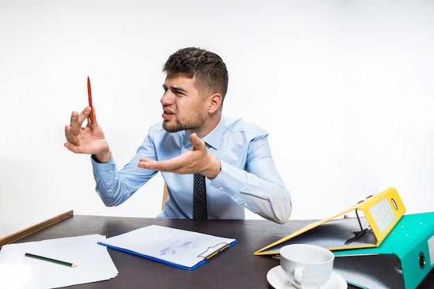 Die tinte im stift endete abrupt und der mann muss mit bleistift schreiben. der junge mann ist absolut wütend und aggressiv. konzept der probleme des büroangestellten, des geschäfts, der werbung, alltäglicher probleme.