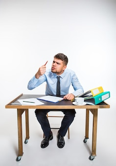 Die tinte in der feder endet abrupt und der mann muss mit bleistift schreiben. der junge mann ist absolut wütend und aggressiv. konzept der probleme des büroangestellten, des geschäfts, der werbung, der alltäglichen probleme.