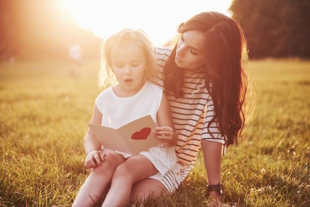 Die tochter des kindes gratuliert ihrer mutter und gibt ihr eine postkarte.