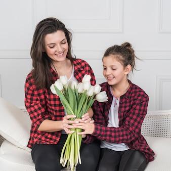 Die tochter, die der mutter auf couch tulpenblumen gibt