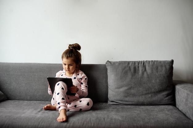 Die tochter sitzt auf der couch und spielt ein spiel auf dem tablet