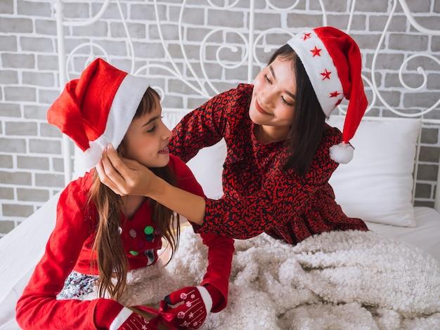 Die tochter und mutter feiern den weihnachtstag im haus