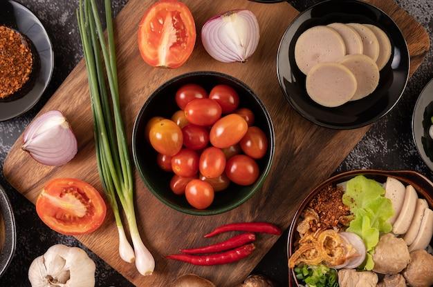 Die tomaten in der schwarzen tasse mit frühlingszwiebeln, paprika, tomaten und roten zwiebeln.