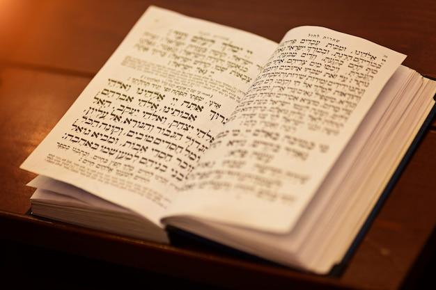 Die torarolle ist das heiligste buch im judentum, das jüdische gebetbuch auf dem tisch