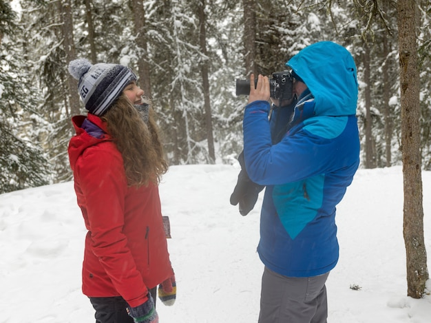 Die touristen, die ein foto im schnee machen, bedeckten wald, johnston-schlucht, banff-nationalpark, alberta, können