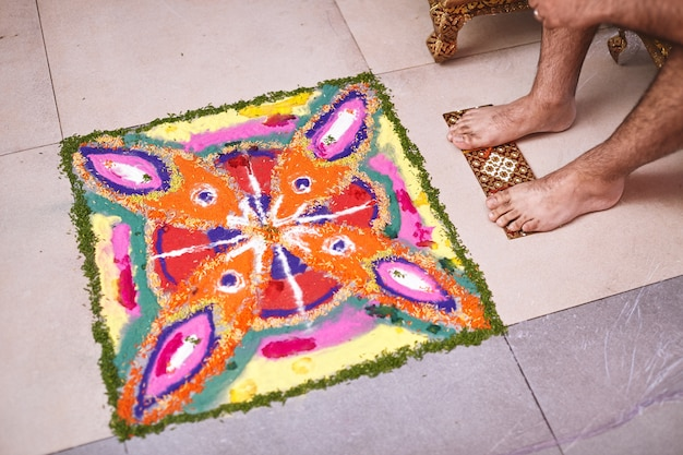 Die traditionelle rangoli kunst, dekoriert mit vielfarbigem reis und den füßen des bräutigams