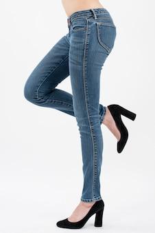 Die tragenden jeans der frau, die aufwerfen, heben ihr bein in seitenansicht halber länge lokalisiert auf weißem hintergrund an