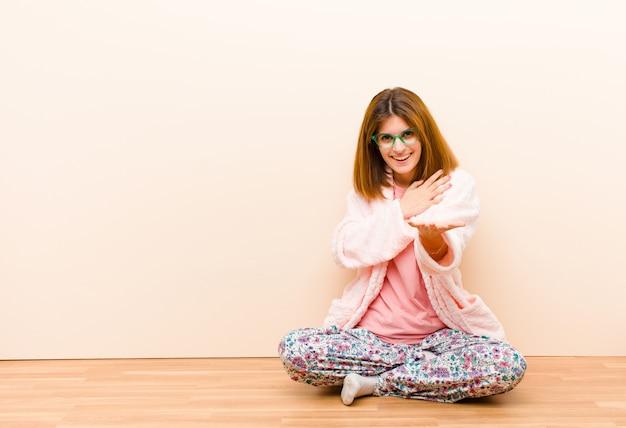 Die tragenden pyjamas der jungen frau, die zu hause sitzen, fühlend glücklich und in der liebe und lächeln mit einer hand nahe bei herzen und der anderen, dehnten ehrlich aus