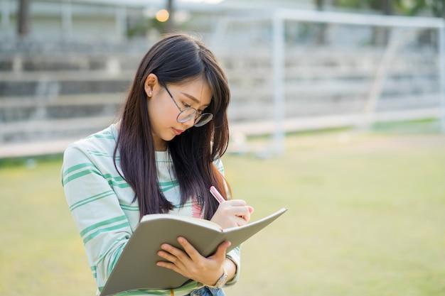 Die tragenden stehenden brillen der jugendlichen schreiben ein notizbuch in fußballplatz bei sonnenuntergang