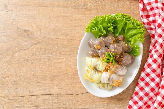 Die transparenten kugeln heißen saku sai moo oder gedämpfter tapioka-knödel-ball mit schweinefleisch-füllung und (kow griep pag mor) gedämpfte schweinereis-päckchen oder gedämpfte reis-haut-knödel