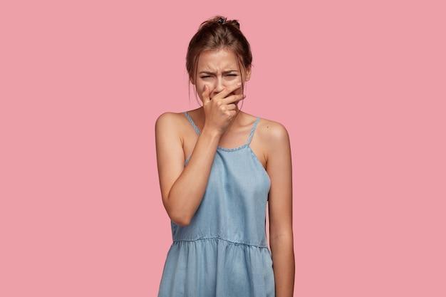 Die traurige, niedergeschlagene, enttäuschte junge frau weint verzweifelt, als sie etwas wertvolles verloren hat, drückt negative gefühle aus, bedeckt den mund, ist unglücklich und bedauert, schlechte worte zu einer nahen person gesagt zu haben