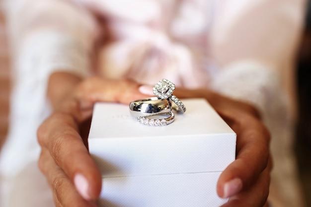 Die trauringe, die vom weißgold und von den diamanten hergestellt werden, liegen auf weißem kasten in den armen der braut